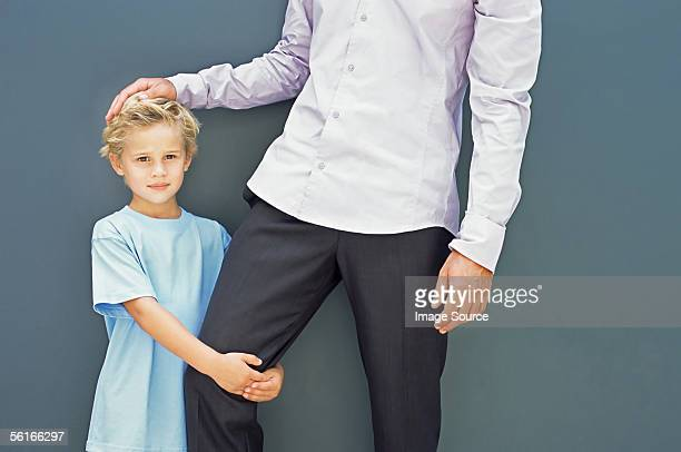 Boy holding his father's leg