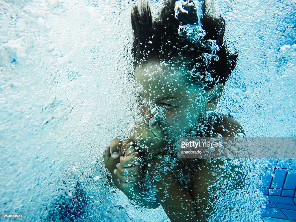 Boy holding his nose, jumping into a swimming pool : Stock Photo