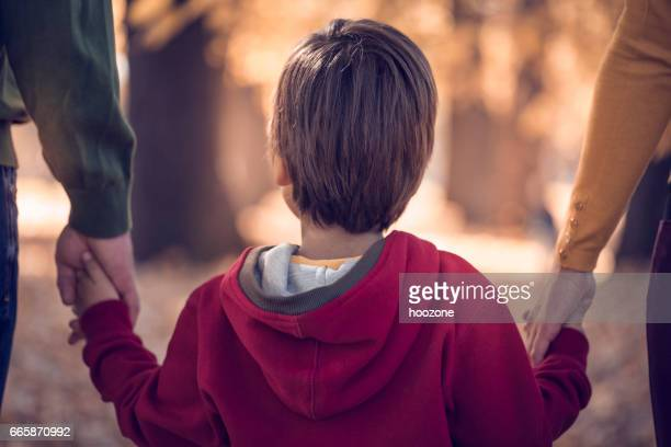 Boy holding his parents hands in park