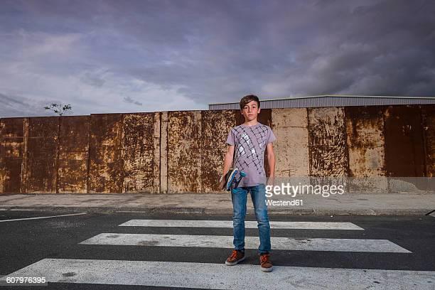 Boy holding his skateboard standing on a zebra crossing
