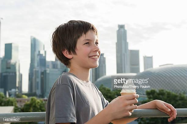 Boy holding ice cream cone, city skyline in background