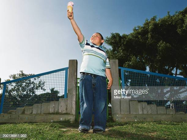 Boy (5-7) holding ice cream cone in air like torch