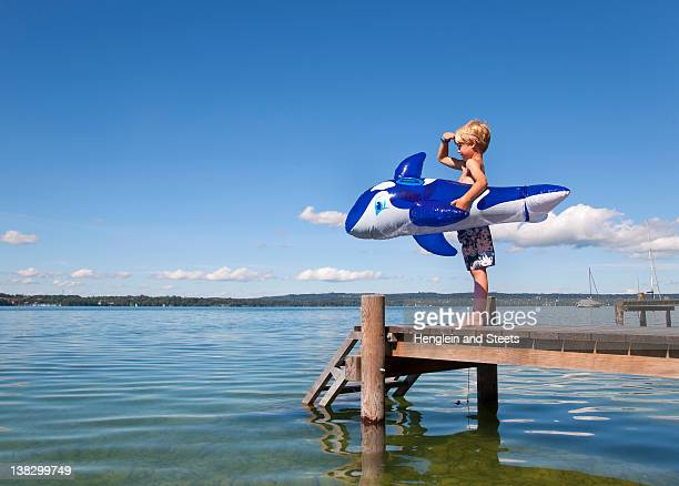 Boy holding inflatable whale on dock