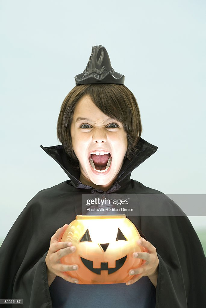 Boy holding jack o' lantern, looking at camera, open mouth, portrait : Stock Photo
