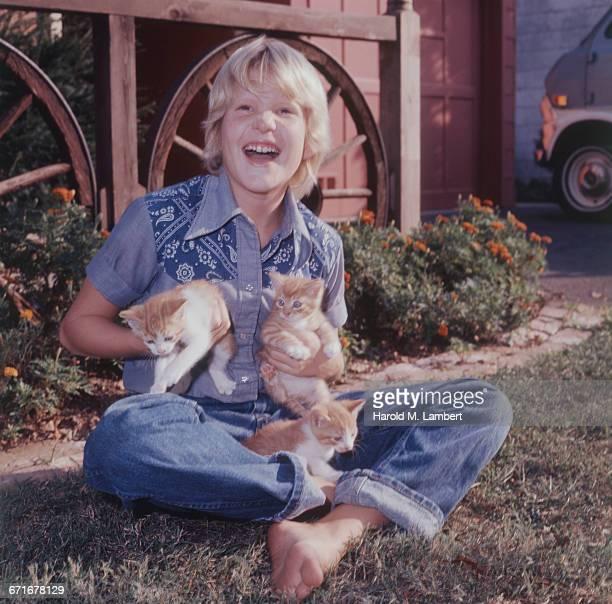 'Boy Holding Kitten, Smiling '