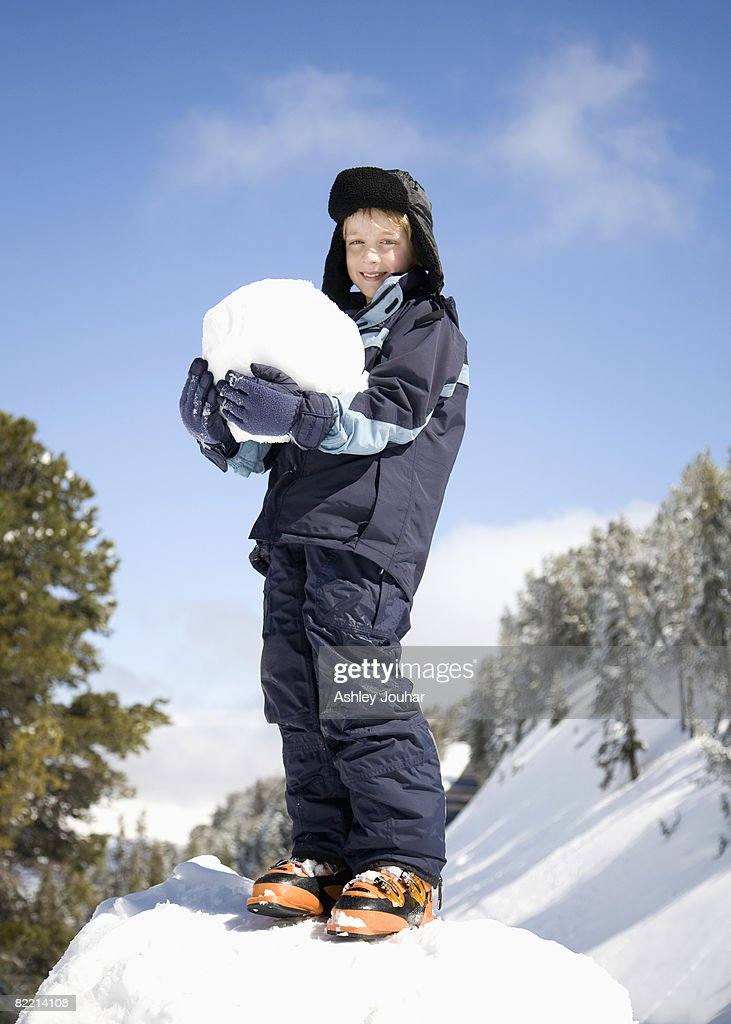 Boy (8-10) holding large snowball : Stock Photo