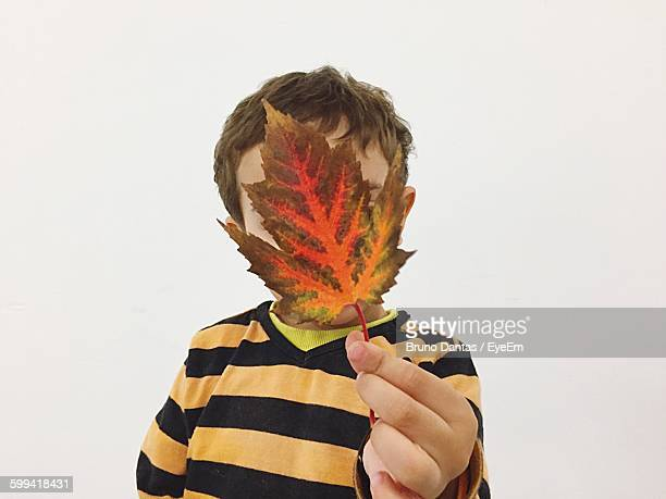 Boy Holding Leaf In Front Of Face Over White Background