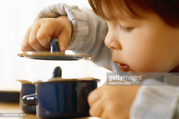 Boy (2-4 years) holding lid, peeping into bowl