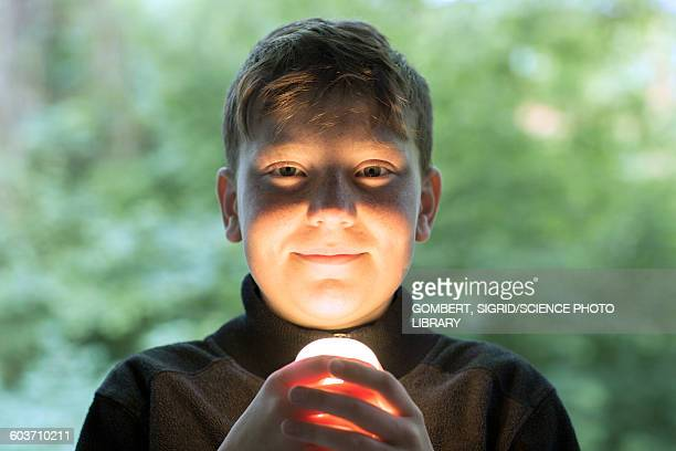 boy holding light bulb - sigrid gombert stock pictures, royalty-free photos & images