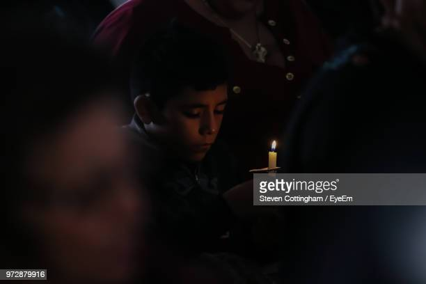 boy holding lit candle in dark - steven cottingham stock-fotos und bilder