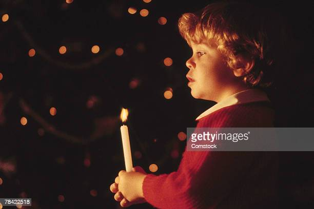Boy holding lit candle