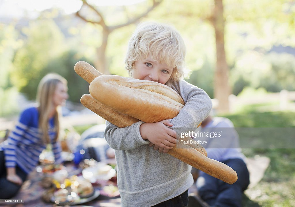 Boy holding loaves of bread outdoors : Stock Photo