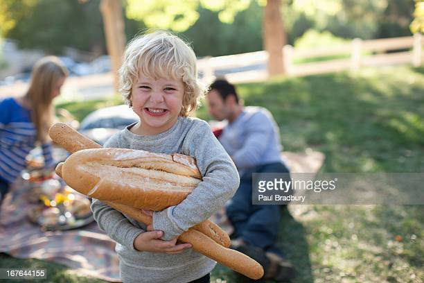 Boy holding loaves of bread outdoors