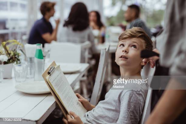 boy holding menu card looking at woman while sitting in restaurant - waiter stock pictures, royalty-free photos & images
