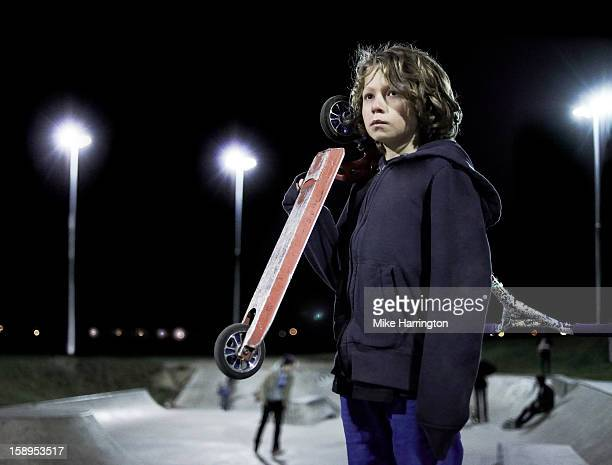 Boy holding micro scooter on top of skate ramp.
