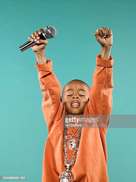 Boy (4-6) holding microphone over head