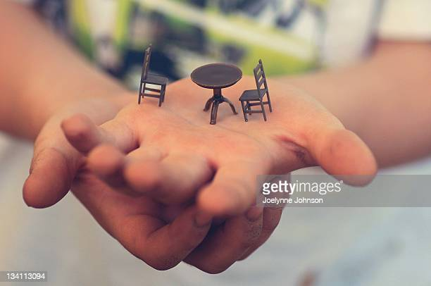 boy holding miniature table and chairs - figurine stock pictures, royalty-free photos & images