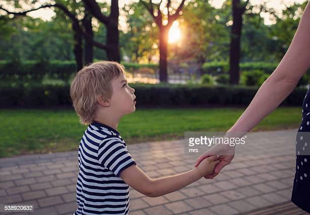 Boy holding mother's hand