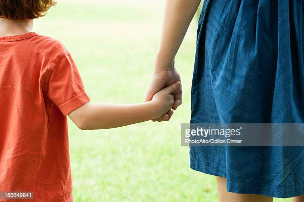 Boy holding mother's hand, rear view