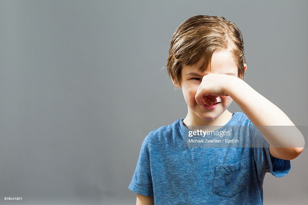 Boy Holding Nose While Standing Against Wall At Home : ストックフォト