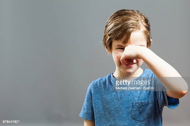 boy holding nose while standing against wall at home - olor desagradable fotografías e imágenes de stock