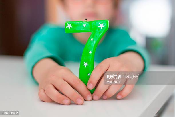 Boy holding number seven birthday candle