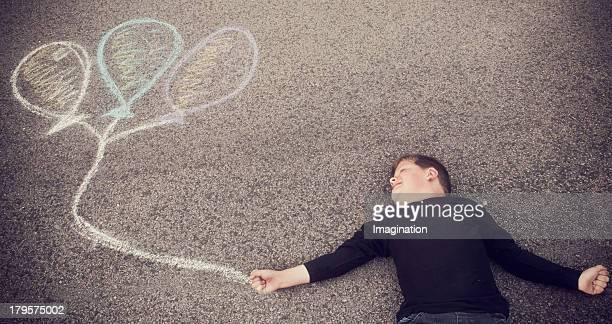 boy holding onto chalk ballons