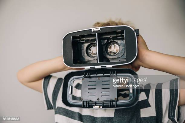 Boy holding open VR glasses before his face to look like a funny robot