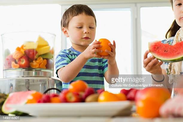 Boy holding orange in kitchen