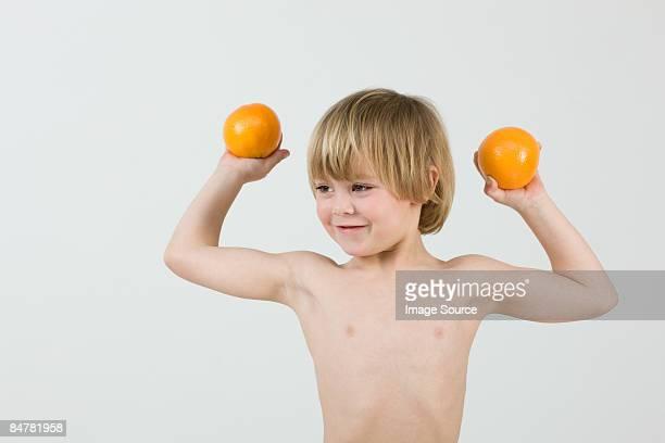 boy holding oranges - blonde forte poitrine photos et images de collection