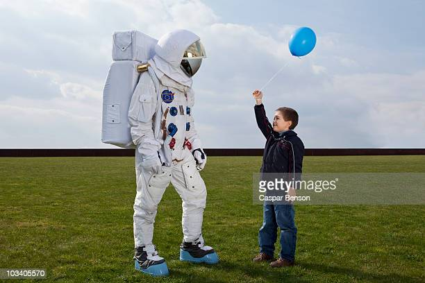 a boy holding out a balloon to an astronaut - space helmet stock photos and pictures