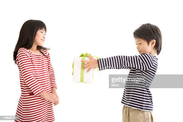 Boy holding out gift box to girl