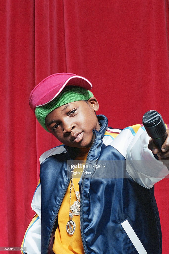Boy (9-11) holding out microphone, close-up : Stock Photo