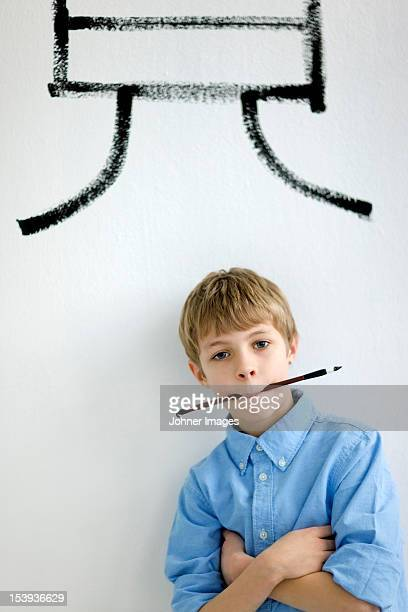 Boy holding paintbrush in mouth