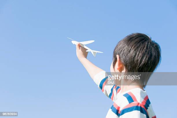 A Boy Holding Paper Airplane