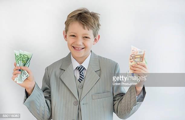 boy holding paper money in his hand, smiling, portrait - banconote euro foto e immagini stock