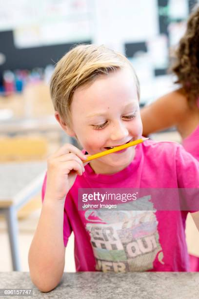 Boy holding pencil in mouth