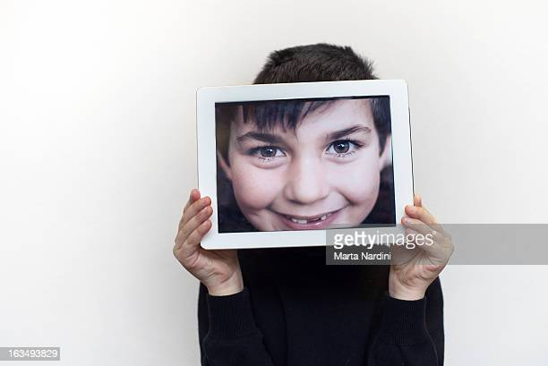 Boy holding picture in  tablet pc
