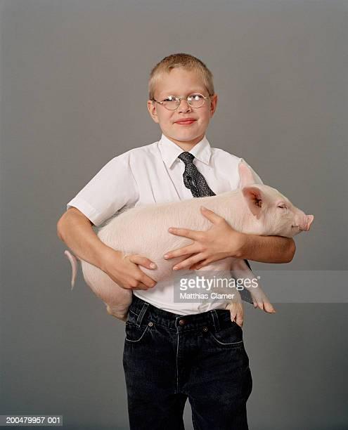 Boy (8-10) holding piglet, portrait