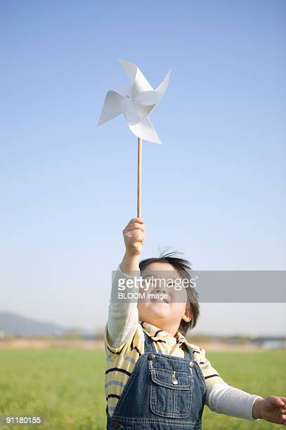 boy holding pinwheel - traditional windmill stock photos and pictures