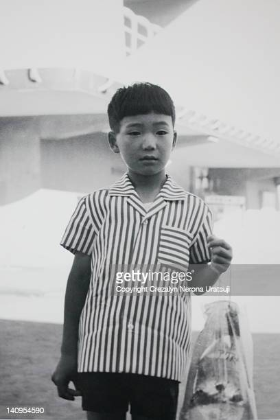 Boy holding plastic bag with goldfish and stone