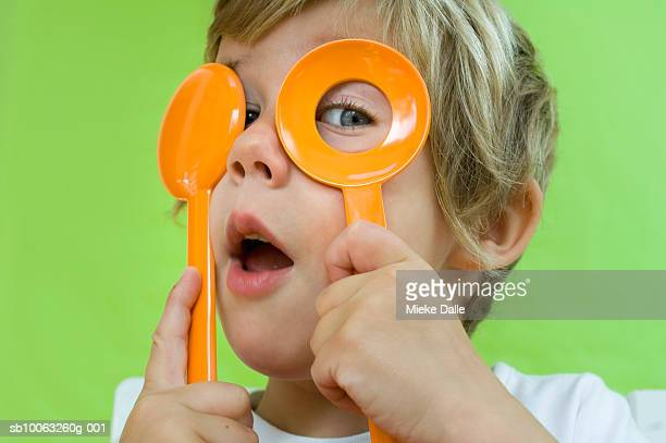Boy (4-5) holding plastic cutlery