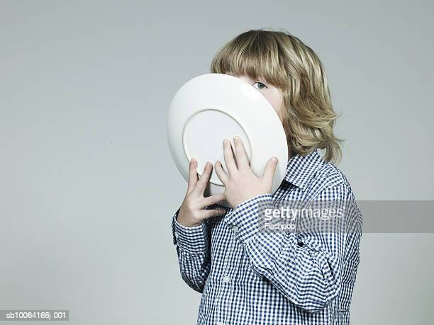 Boy (6-7) holding plate near mouth, looking away