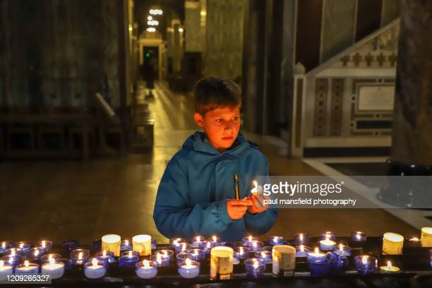 boy holding prayer candle in church - candle of hope stock pictures, royalty-free photos & images