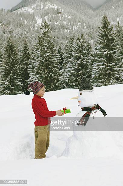 Boy (8-10) holding present out to snowman, side view