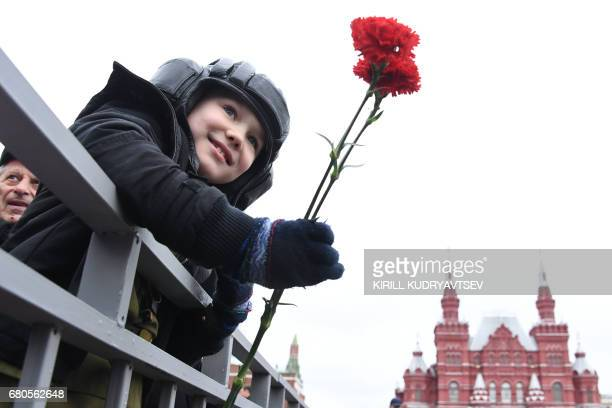 TOPSHOT A boy holding red carnations waits for the Victory Day military parade at Red Square in Moscow on May 9 2017 Russia marks the 72nd...