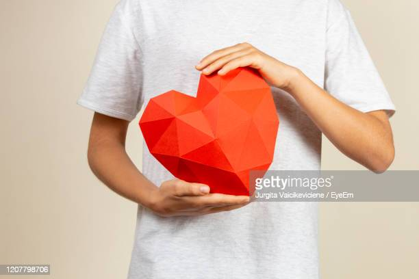 boy holding red polygonal paper 3d heart in his hands. - giving tuesday stock pictures, royalty-free photos & images