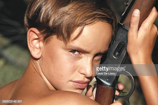 Boy (8-9) holding rifle, close-up