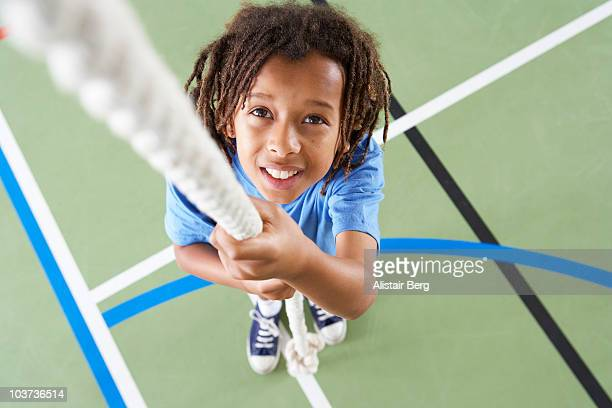 Boy holding rope in gymnasium