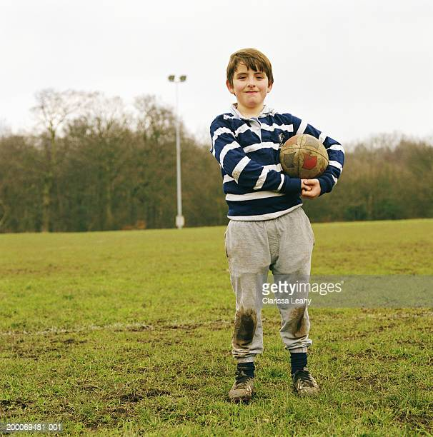 boy (6-8) holding rugby ball under arm on playing field, portrait - rugby pitch stock pictures, royalty-free photos & images